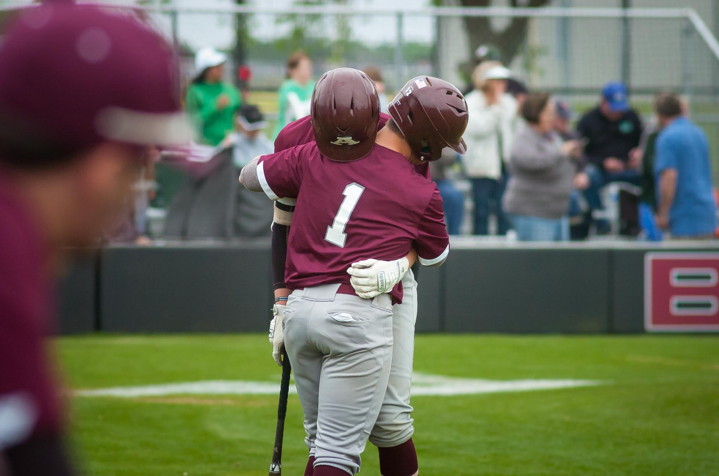 Richard R. Barron   The Ada News -- Ada's Carter Freeland and Hunter Condon (1) share a hug after the final out was made in the Cougars' 11-2 loss to Bishop McGuinness Saturday in Game 3 of their best-of-three Class 4A Bi-District series at Cougar Field.
